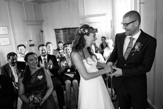 Ein Brautpaar hält sich bei der Trauung an den Händen und lacht.