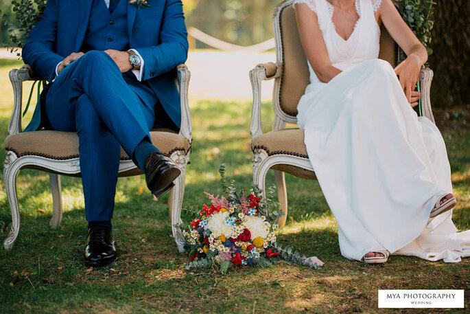 Des mariés assis sur de jolies chaises pendant leur cérémonie laïque, le bouquet de la mariée à leurs pieds.