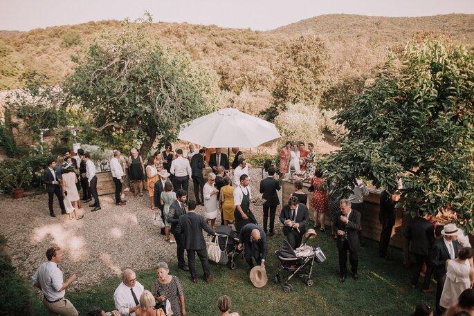 Les invités d'un mariage discutent dans un parc ombragé