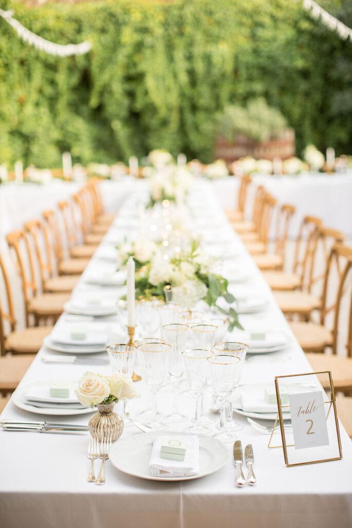 Table dressée pour un mariage champêtre avec des chaises en bois, des bouquets de fleurs blanches, des couverts en argent et des assiettes blanche