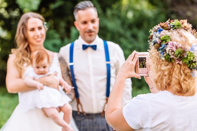 Das Brautpaar mit ihrer Tochter, ein Gast macht ein Foto von ihnen.