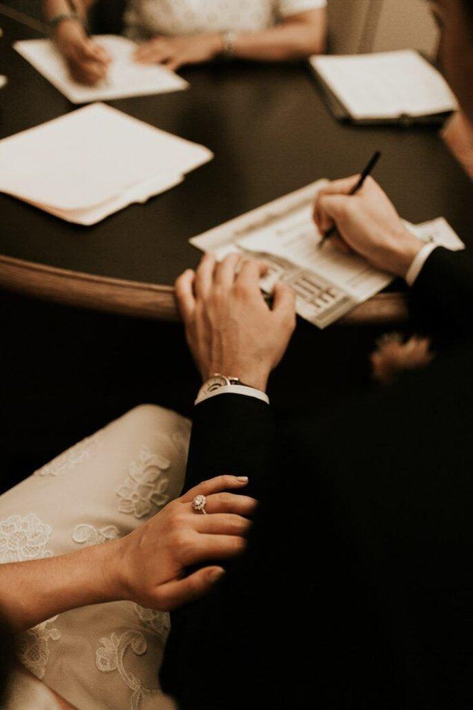 Bräutigam unterschreibt Dokumente während der standesamtlichen Trauung