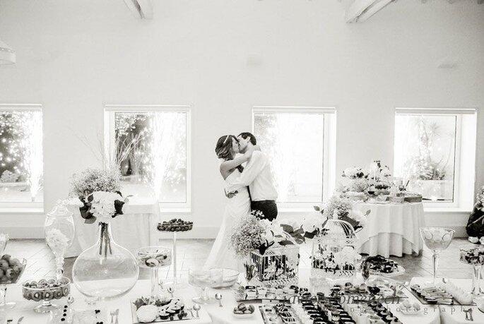 noivos perante mesa a beijarem-se sala com comida casamento