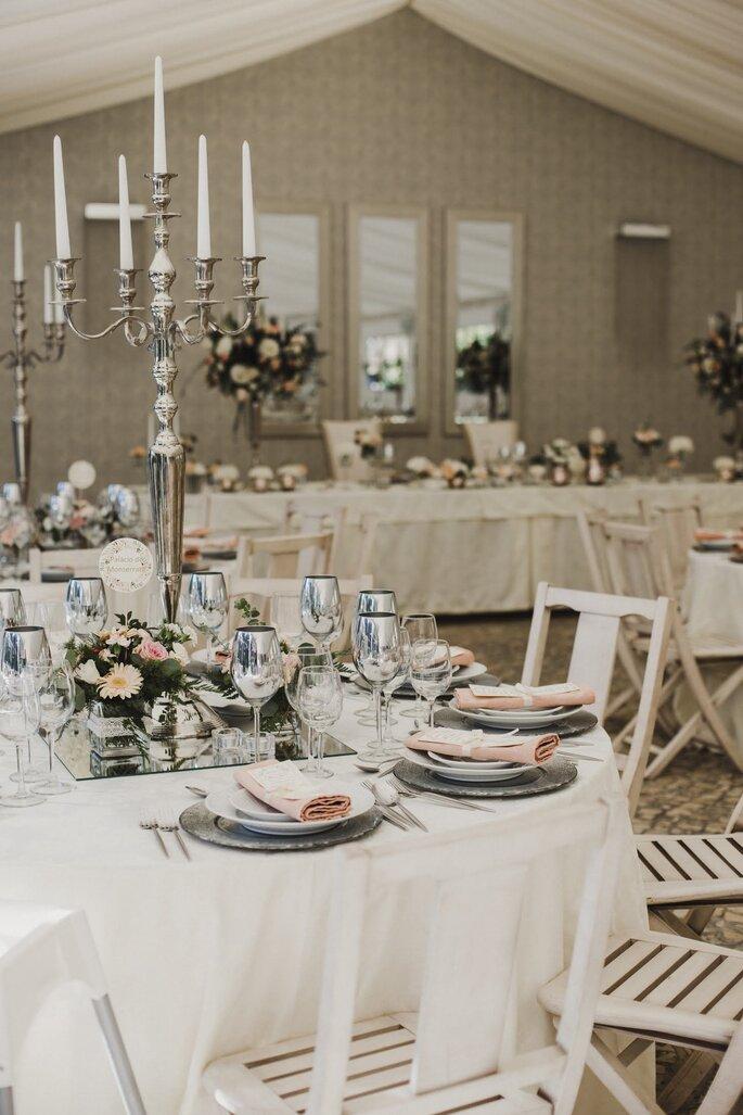 sala casamento em tons pasteis com candelabros nas mesas