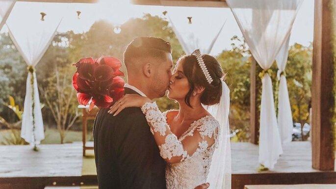 Beijo do casal com o pôr do sol como pano de fundo