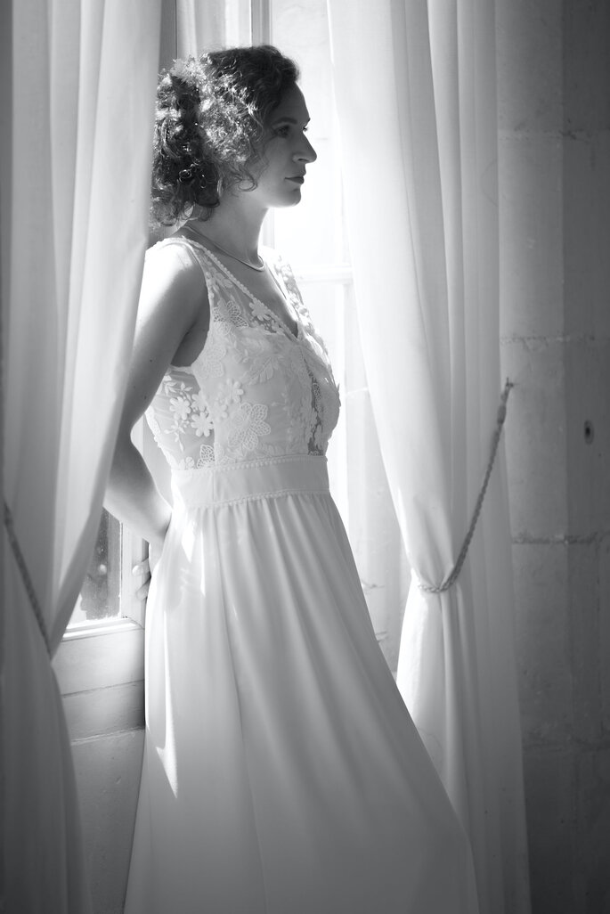 Une mariée portant une couronne de fleurs dans les cheveux et une robe de mariée signée Un Soupçon d'Émilie.