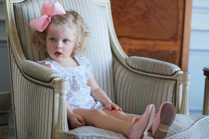 menina numa cadeira com macacão cores suaves e laço grande na cabeça vestido festa casamento