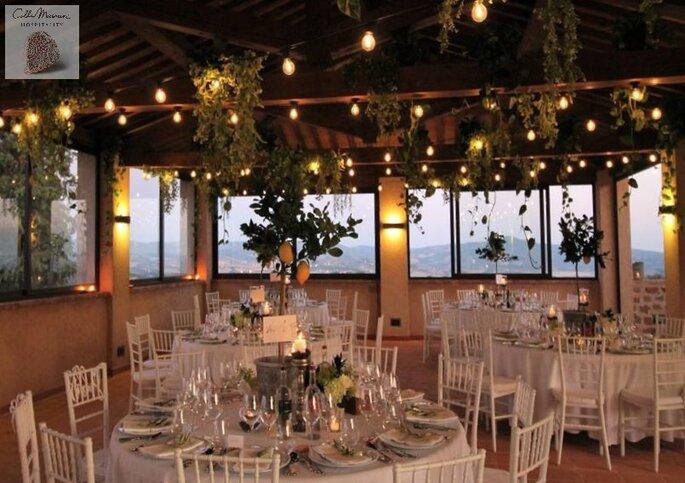 Une salle de restaurant décorée pour un mariage, avec une superbe vue sur la campagne toscane
