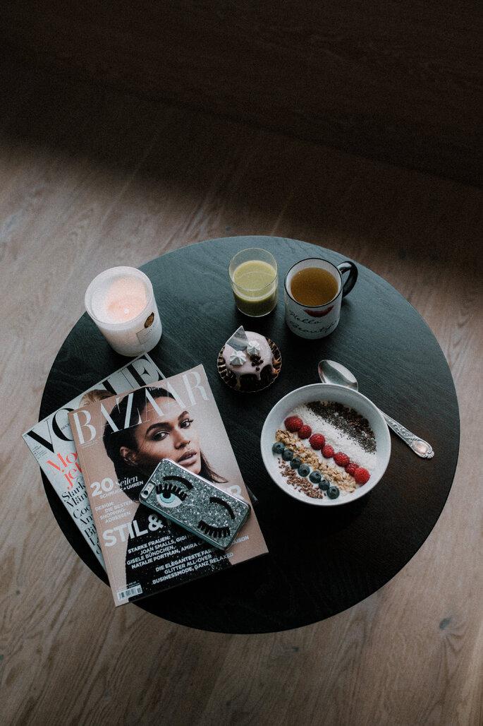 Ein Café-Tisch mit verschiedenen Zeitschriften, Getränken und eine Frühstücksbowl.