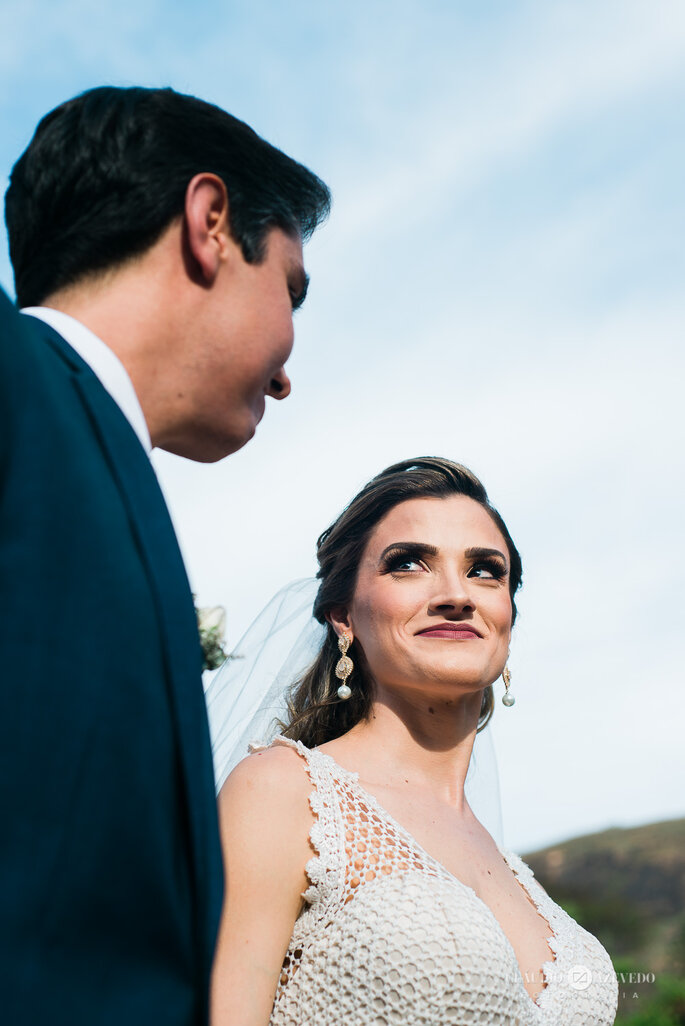 Noivos se olham em casamento no campo