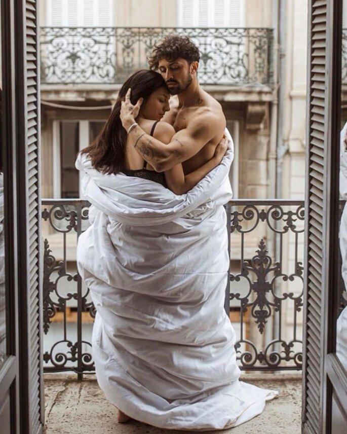 Paar auf Balkon sich umarmend mit Decke