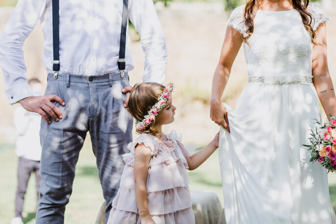 noivos com criança menina com vestido folhos e coroa de flores casamento