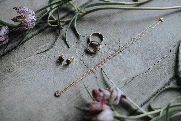 Ohrringe, Eheringe & Kette gemeinsam mit Blumen auf einem Holztisch, organisiert von Freakin' Fine Weddings.