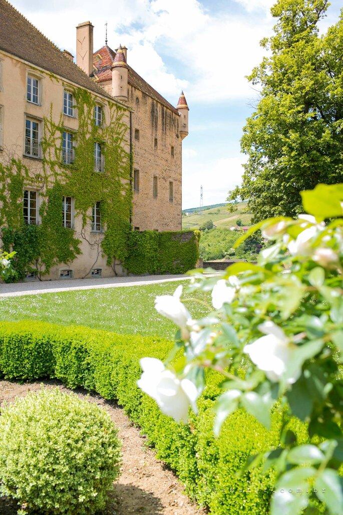Façade d'un château avec de grandes fenêtres, entouré d'un parc paysager