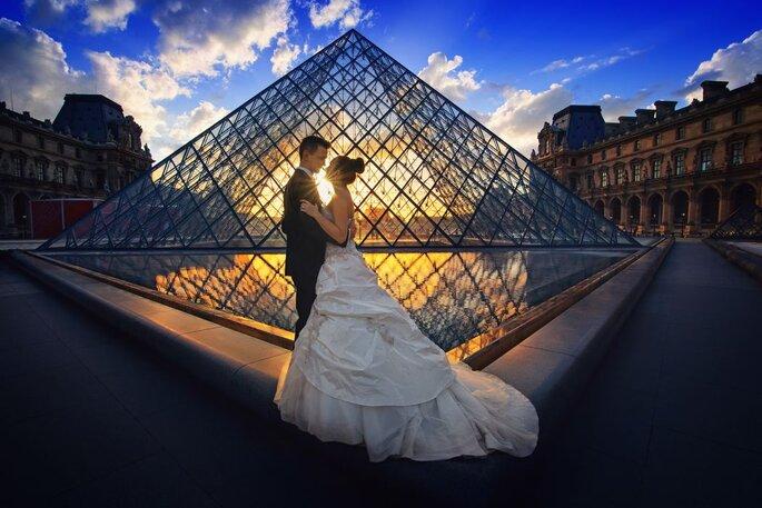 Deux mariés photographiés devant la pyramide du Louvre au coucher du soleil grâce à leur wedding planner