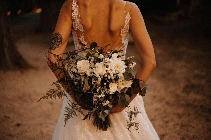 Une mariée tatouée avec un superbe bouquet de fleurs blanches et de végétaux