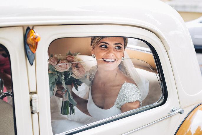 noiva a sorrir dentro do carro com bouquet na mão