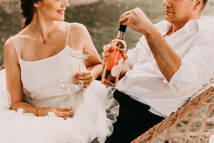 Elopement Fun Wedding Shooting Setting Picknick Brautpaar in Haengematte anstoßend