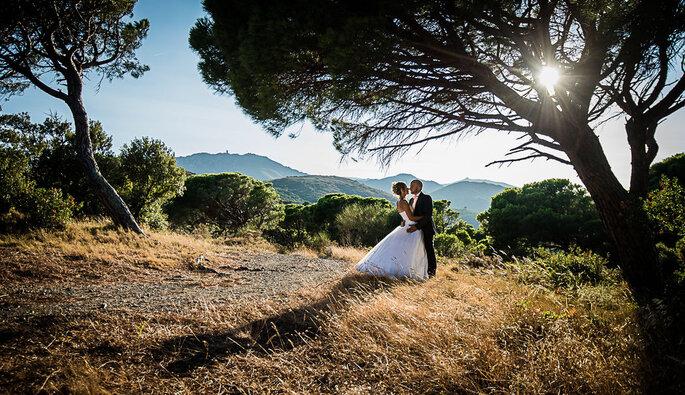 Un couple de mariés enlacés pose au milieu d'un paysage typique du sud