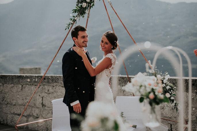Ma petite cérémonie - Deux mariés dans un instant de complicité sous une arche tipi fleurie, face aux montagnes