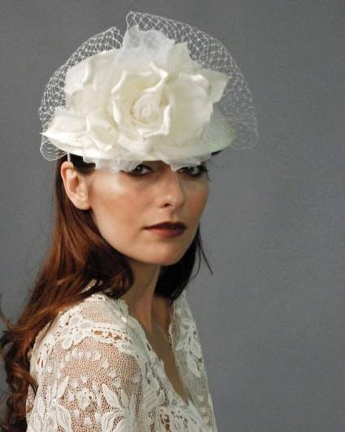 Sombrero para novia con velo jaula y una flor voluminosa. Foto: www.louisegreen.com