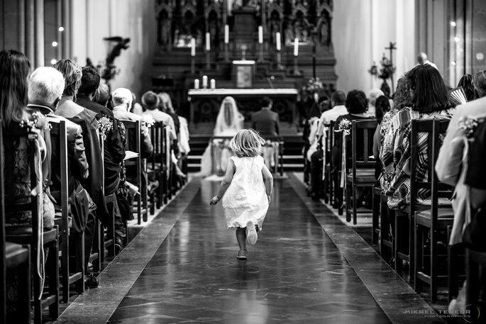 Une petite fille court dans l'allée de l'église pendant un mariage