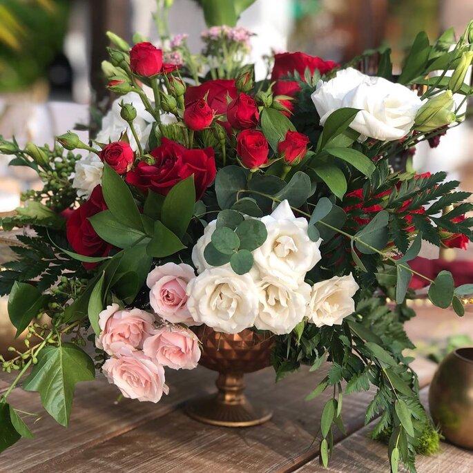 Decoración para mesas con rosas rojas, blancas, rosas y follaje verde.