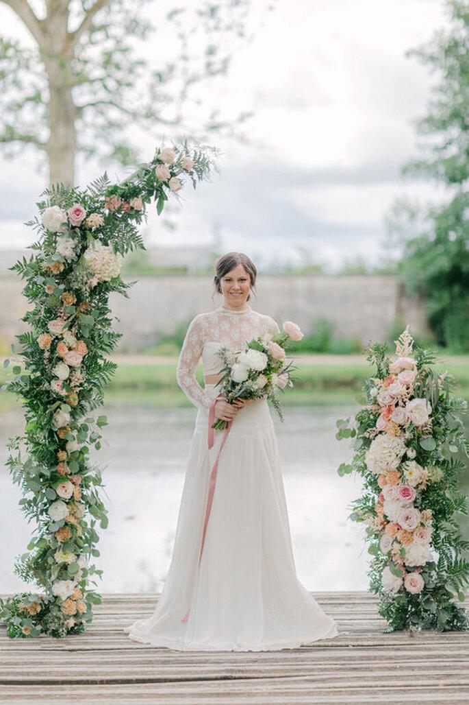 La mariée, bouquet à la main, prend la pose dans un décor fleuri et un climat pluvieux.