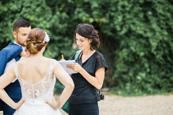 Léonie le jour d'un mariage, prenant des notes auprès des invités.