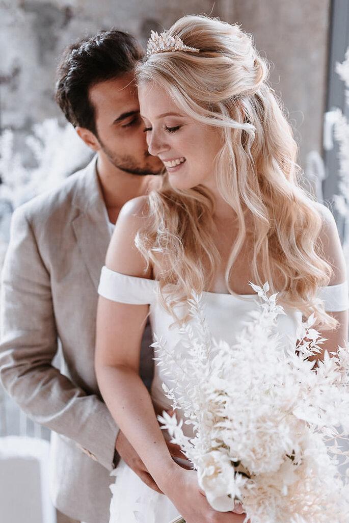Brautpaar sich umarmend mit Brautstrauß
