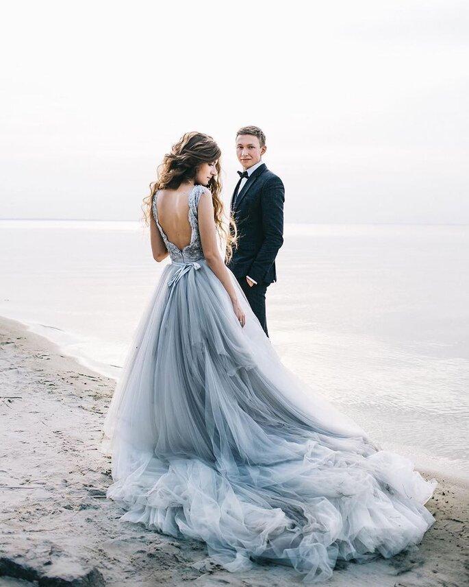 noiva com vestido de noiva azul cinzento na praia com o noivo