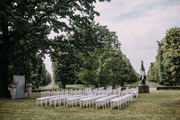 gausfotografie.de: Lange Stuhlreihen bei der Hochzeit unter freiem Himmel im Garten des Herrenhauses.