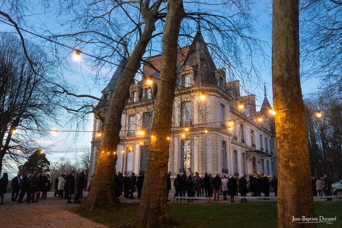 Le Château de Santeny en arrière-plan, de nuit, derrière des guirlandes guinguettes accrochées à des arbres, avec les invités dehors pour un vin d'honneur