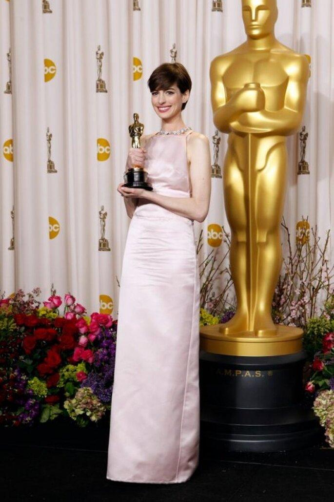 Anne Hathaway en un vestido largo en color rosa palo con corte recto y escote cuadrado - Foto Prada Facebook