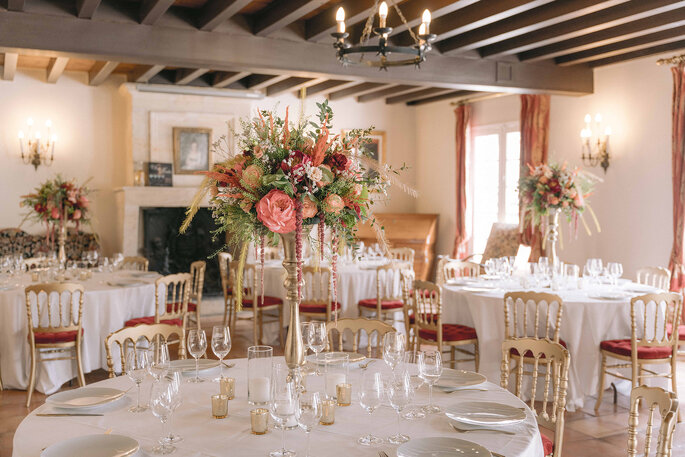 Une salle de réception décorée pour un mariage avec ces bougeoirs, des vases fleuris et des chaises dorés