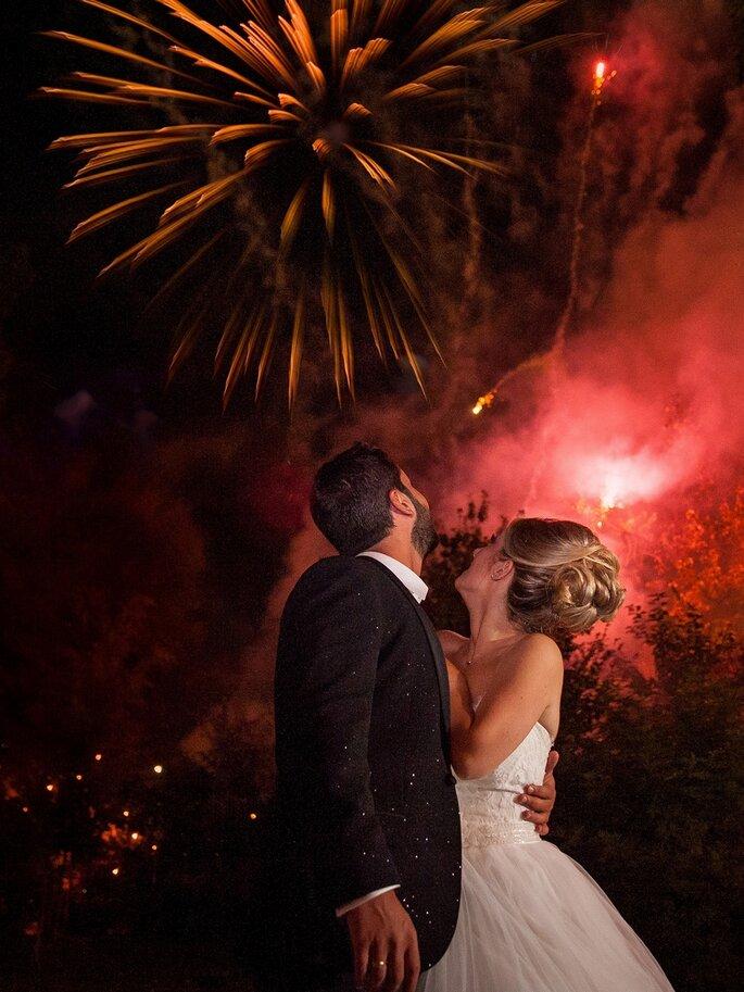 Un couple de mariés enlacés à la lueur d'un superbe feu d'artifice