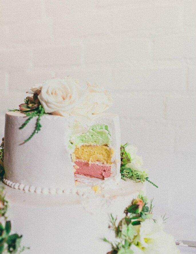 Pastel de boda con cobertura tradicional y tres capas de bizcocho de colores. Foto: Sweet Little Photographs