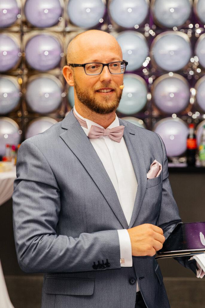Ein Mann mit Brille und Anzug bei einer Hochzeit.