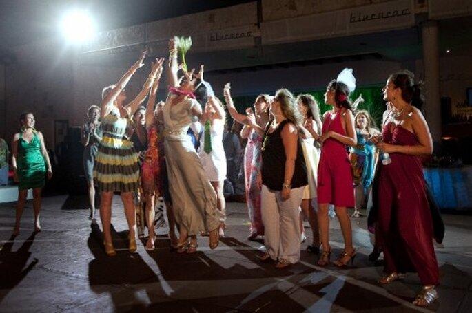 Novia lanzando el ramo en la recepción de boda - Foto Natalia Martínez