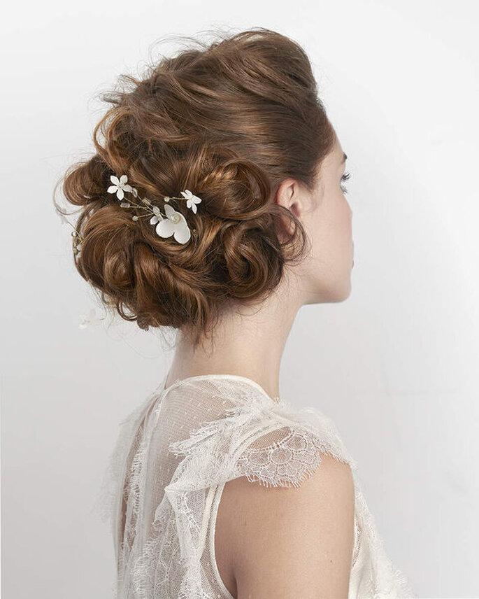 Un superbe chignon de marié décoiffé et structuré avec un accessoire en forme de fleurs