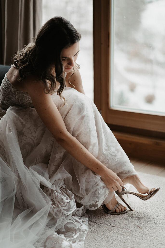 Die Braut zieht die Brautschuhe an.