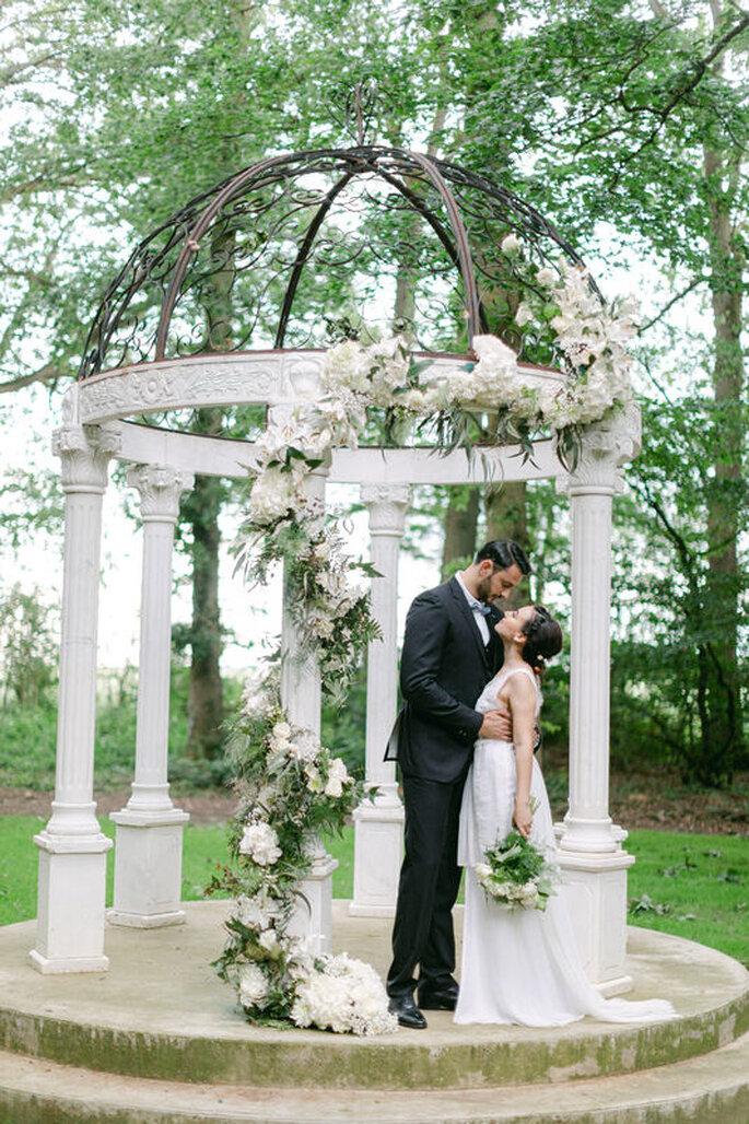 Les mariés s'embrassent sous une coupole, théâtre de leur cérémonie.