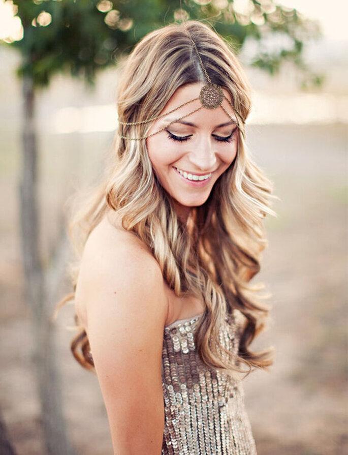Une mariée avec une coiffure pour cheveux longs et ondulés avec un bijou de tête