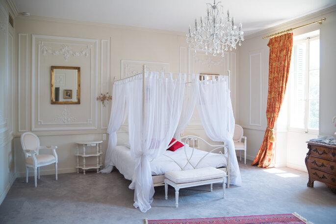Une chambre avec un lit baldaquin où pourront dormir des invités après un mariage