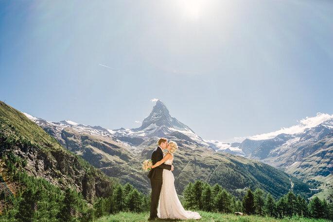 hochzeitspaar steht vor einem berg