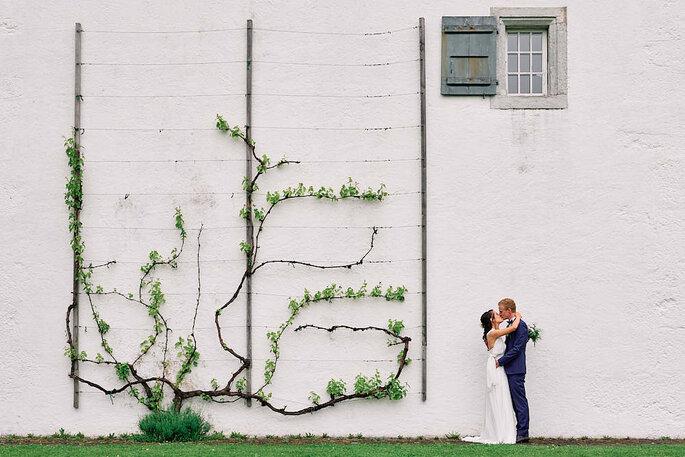 Ein Brautpaar küsst sich vor einer weißen Wand, an der Efeu rankt.