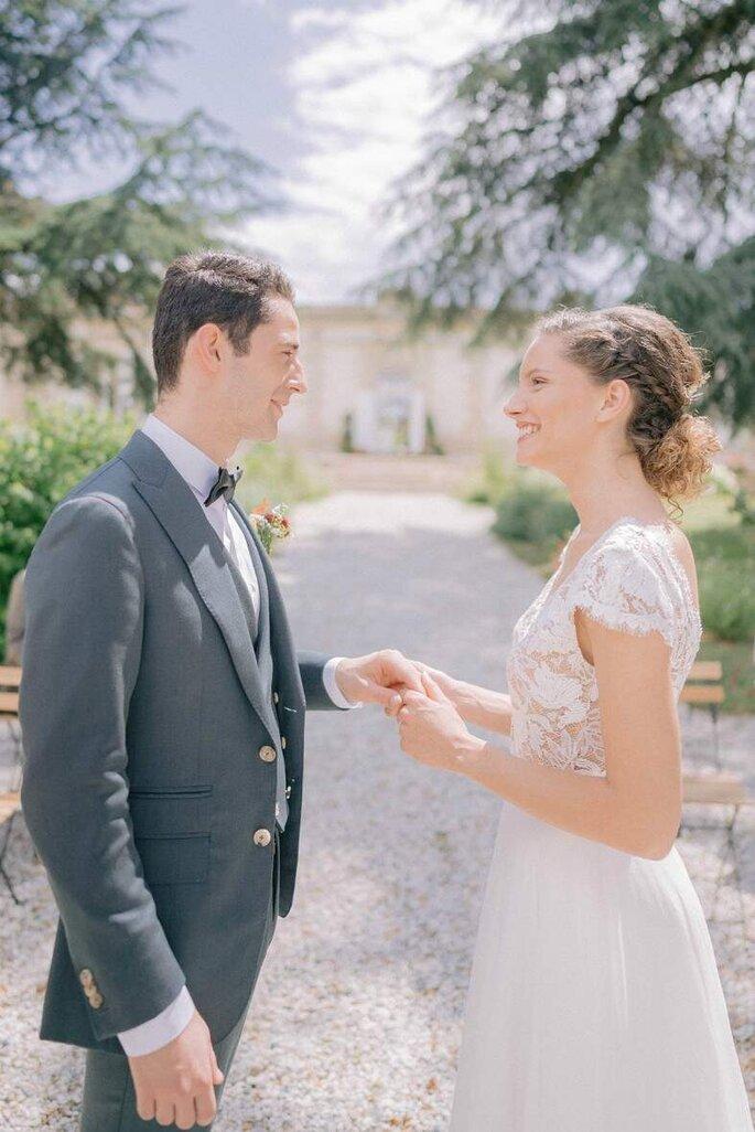 Un couple de mariés se tient la main en se souriant devant une allée bordée de verdure