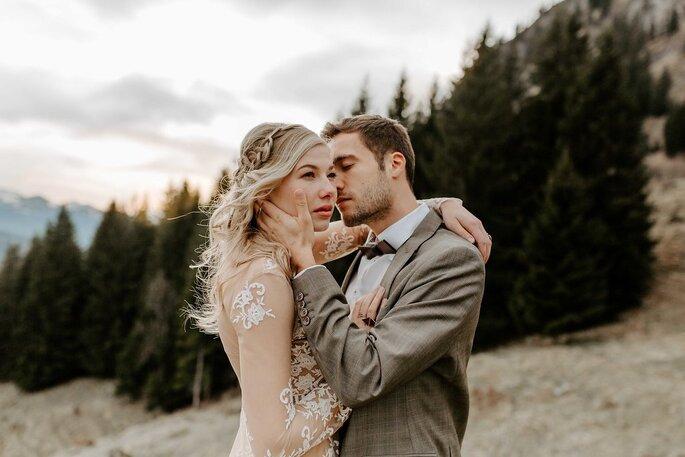 Bräutigam küsst Braut in den Bergen
