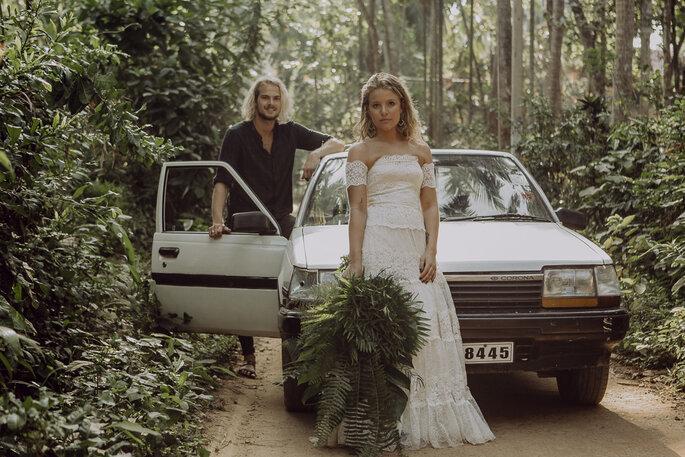 Das Brautpaar vor einem Vintage-Auto.