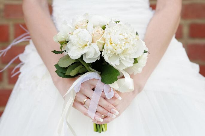 Novia sosteniendo un ramo de rosas blancas. Foto vía Shutterstock